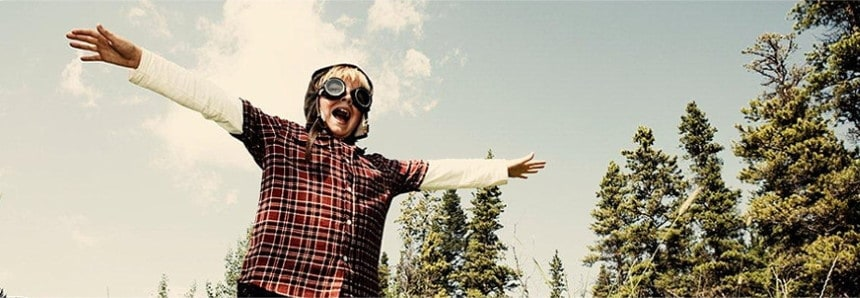 Young boy in flyiong goggles and plaid shirt pretends to fly